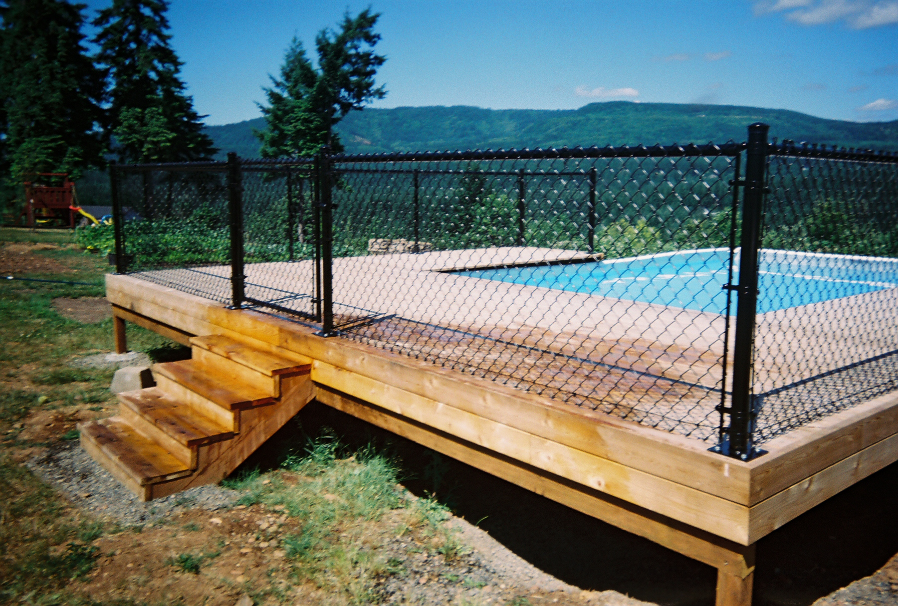 Gated Black Vinyl chain link fence with flange post. Contact Vancouver Washington's Best Fence Builders. The Fenceman Fence Company installs wood, vinyl, chain link and ornamental iron fences. We also offer materials for the do it yourselfer.