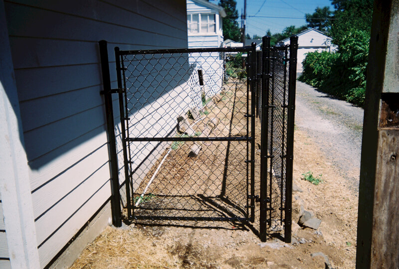 Black Vinyl Chain Link Walkway Gate. The Fenceman Fence Company installs wood, vinyl, chain link and ornamental iron fences. We also offer materials for the do it yourselfer.