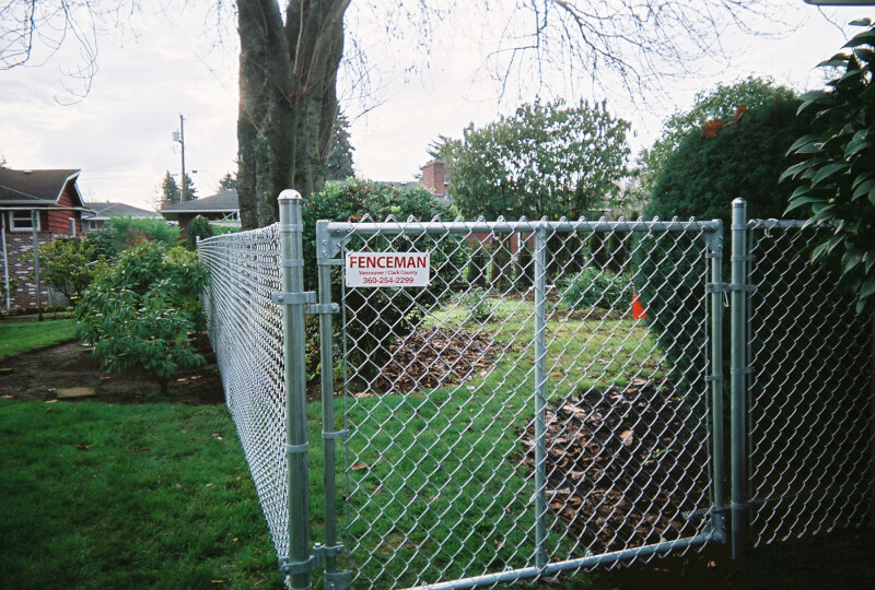 Extra Wide Chain link gate for riding lawn mower access. The Fenceman Fence Company installs wood, vinyl, chain link and ornamental iron fences. We also offer materials for the do it yourselfer.