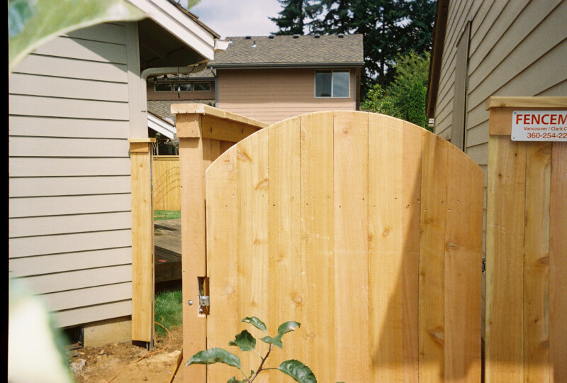 Arch top gate with top cap. The Fenceman Fence Company installs wood, vinyl, chain link and ornamental iron fences. We also offer materials for the do it yourselfer.