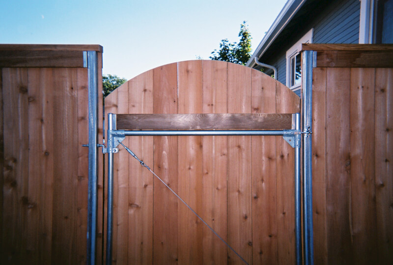 Steel framework for wood gate with Top gate fence and Arch gate. The Fenceman Fence Company installs wood, vinyl, chain link and ornamental iron fences. We also offer materials for the do it yourselfer.