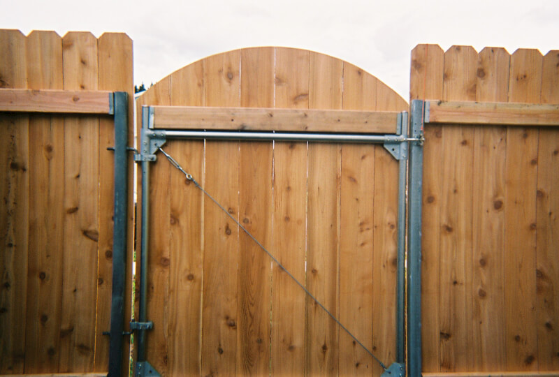 Dog ear fence with arch gate. The Fenceman Fence Company installs wood, vinyl, chain link and ornamental iron fences. We also offer materials for the do it yourselfer.