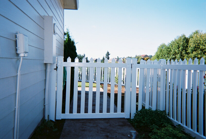 White Picket Vinyl fence and gate. The Fenceman Fence Company installs wood, vinyl, chain link and ornamental iron fences. We also offer materials for the do it yourselfer.