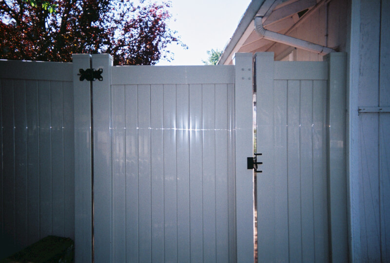 White Vinyl Access gate. The Fenceman Fence Company installs wood, vinyl, chain link and ornamental iron fences. We also offer materials for the do it yourselfer.